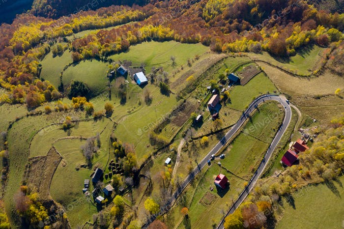 Aerial view of epic countryside road and autumn forest from above