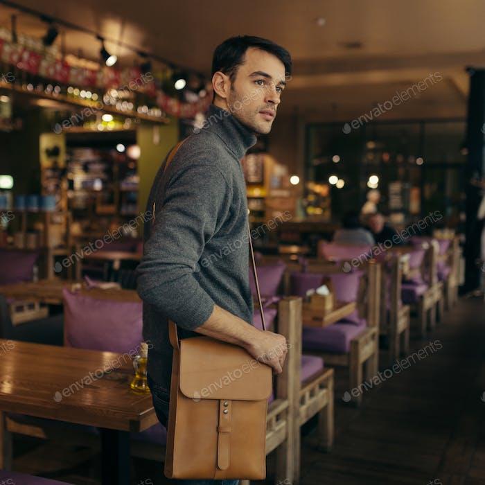Handsome businessman with leather bag on his shoulder