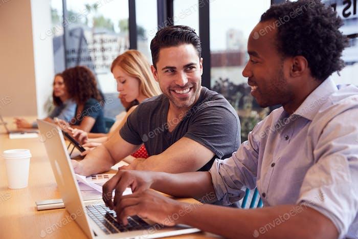 Geschäftsleute und Geschäftsfrauen, die im freigegebenen offenen Büroarbeitsbereich arbeiten
