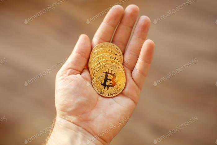 hand holding shiny golden bitcoins, gold money