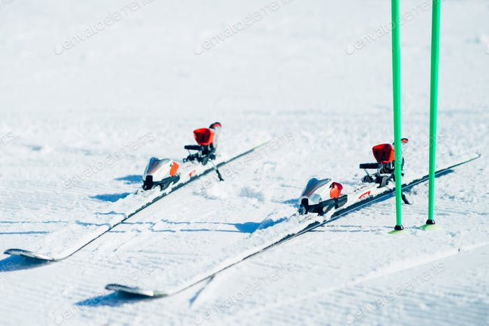 Skis and poles sticking out of the snow closeup