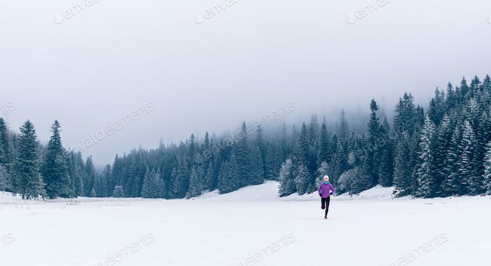 Woman running on winter trail in forest, fitness inspiration