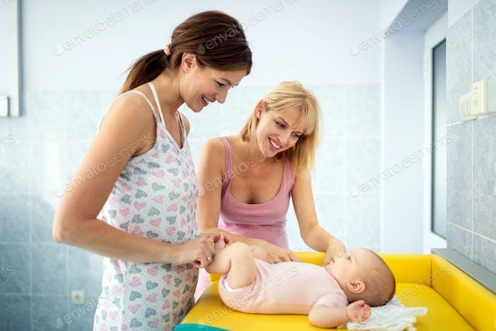 Schwester besucht eine junge Mutter mit ihrem Neugeborenen im Krankenhaus