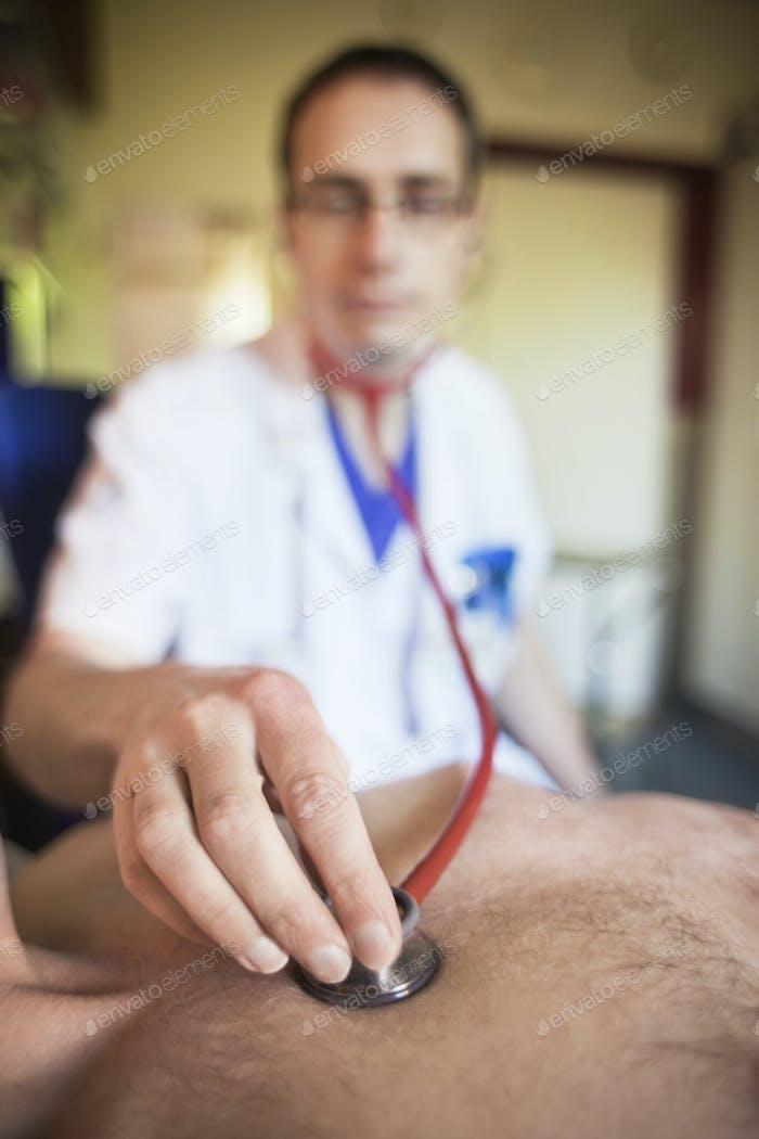 Nahaufnahme des Arztes Positionierung Stethoskop auf männlichen Patienten im Krankenhaus
