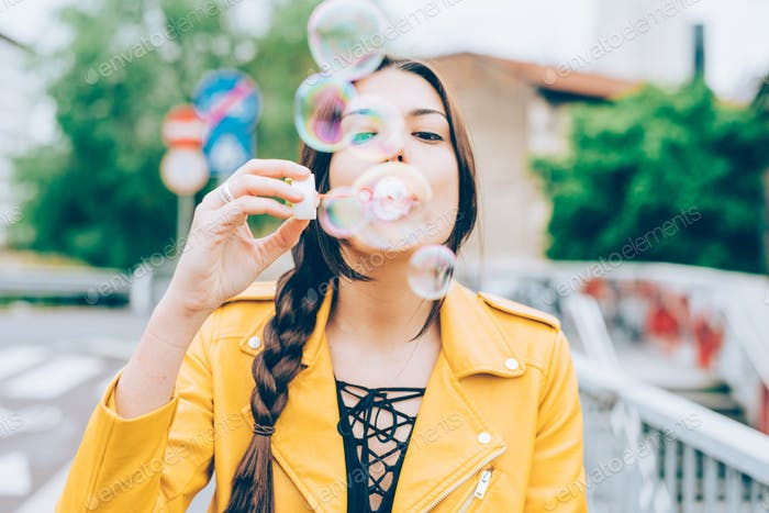 Hipster woman playing with bubble soap