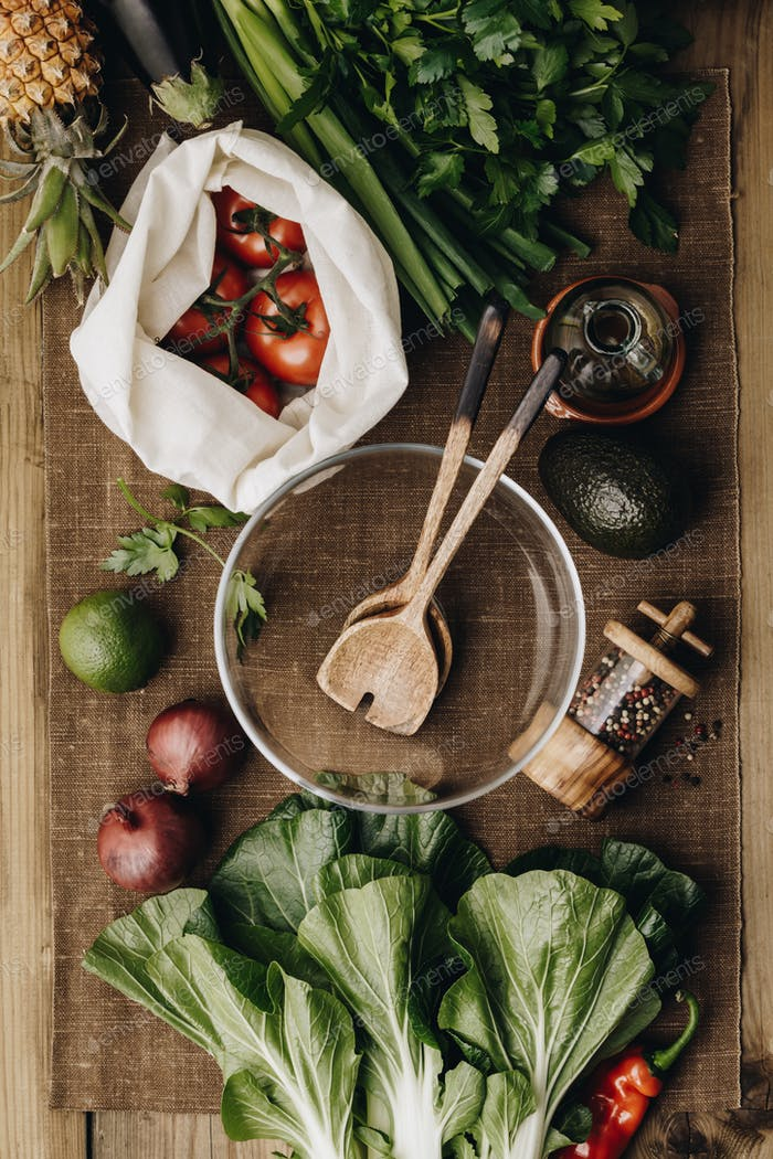 Fresh organic ingredients for salad making on rustic background