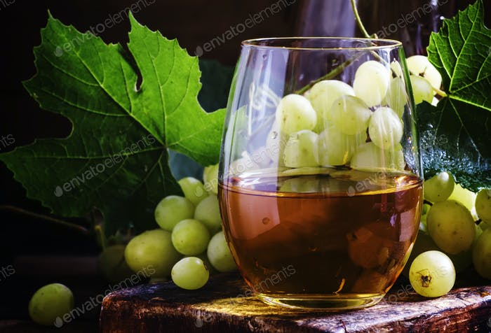 White wine in a glass, green grapes with leaves in a wine cellar