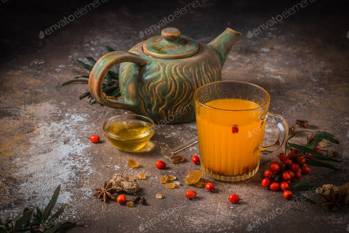 Autumn berry tea in glass cup with tea pot