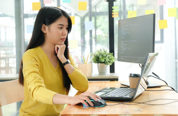 Female programmer using laptop to create programs for clients.