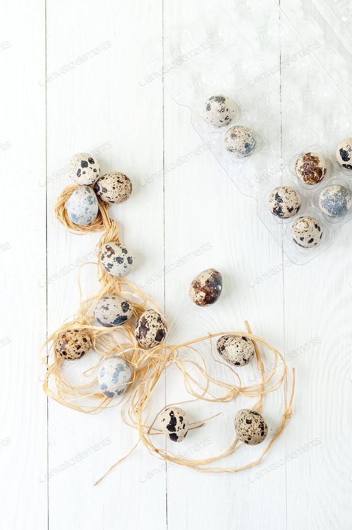 Fresh quail eggs on a white wooden table.