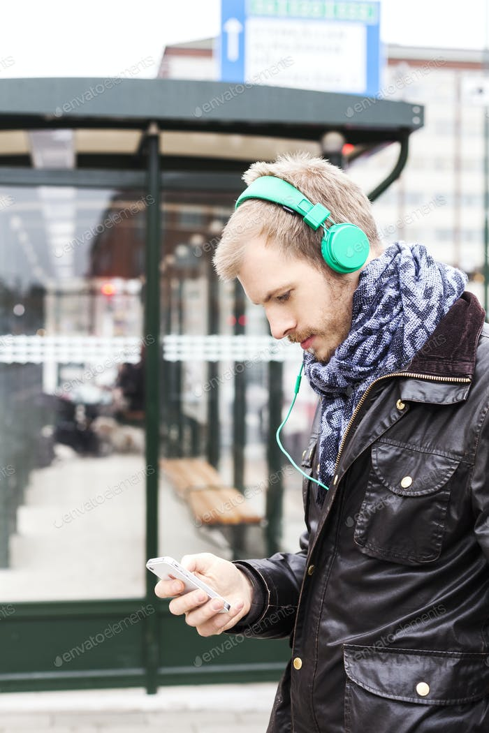 Side view of man listening music through mobile phone while waiting at bus stop