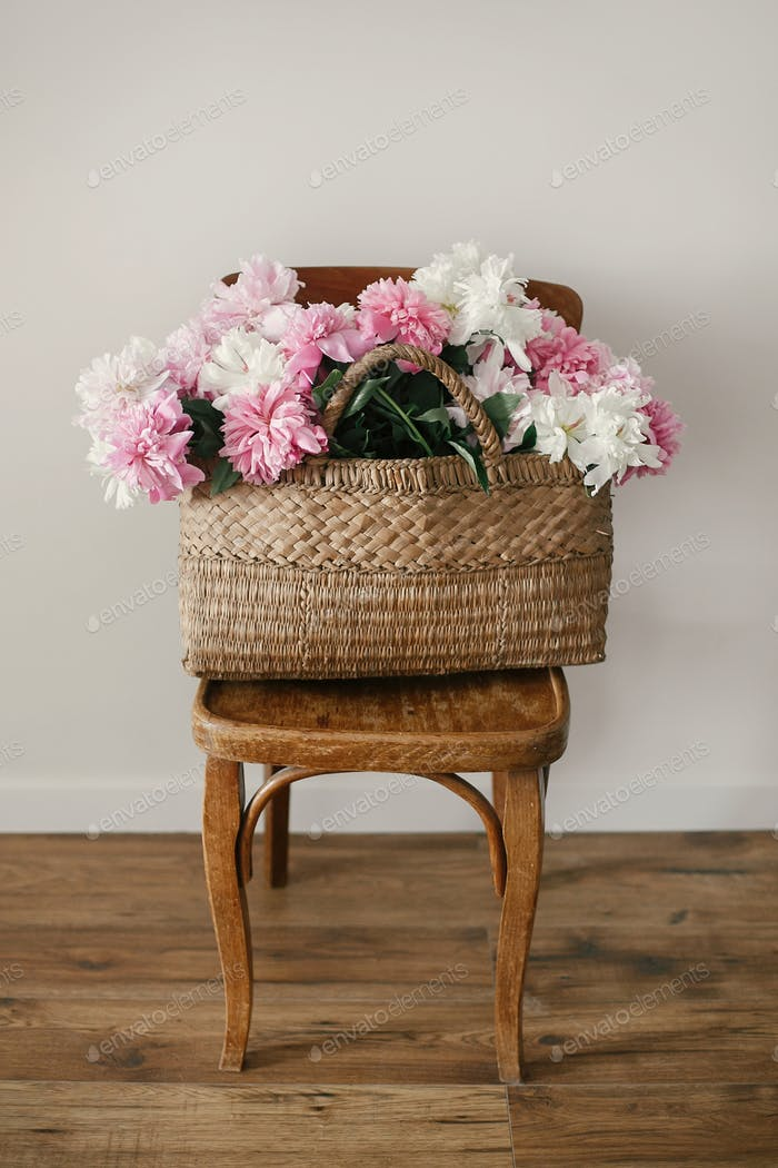 Stylish  pink and white peonies in straw bag on wooden rustic chair in room