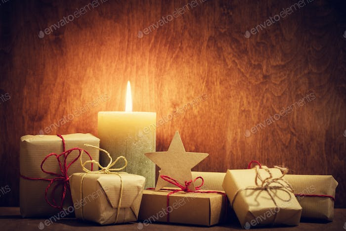 Chistmas presents, gifts with a candle glowing on wooden wall background.