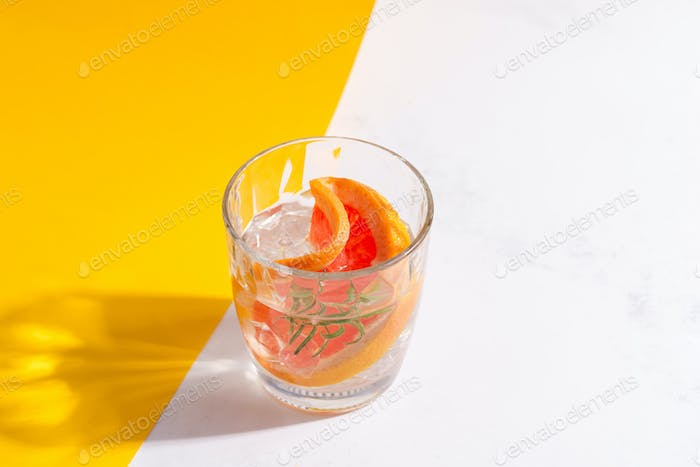 Refreshing cold summer drink in a glass with slice of grapefruit and ice cubes on a duotone yellow