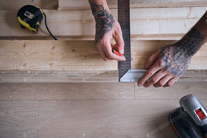 A man with tattooed arms measuring board.