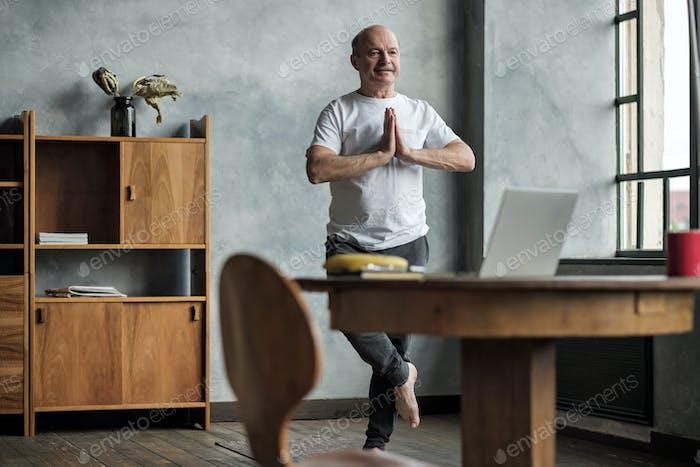 Thumbnail for Senior hispanic man standing in one leg yoga balance.