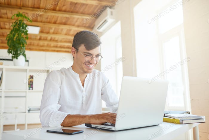 cheeful confident young businessman wears white shirt and spectacles