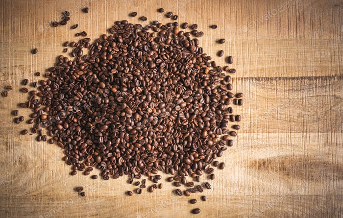 Roasted brown coffee beans spilled on wooden table background.