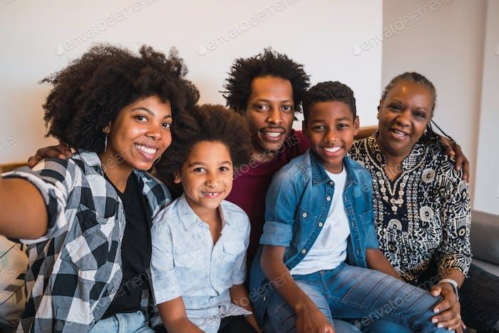 Multigenerational family taking selfie at home.