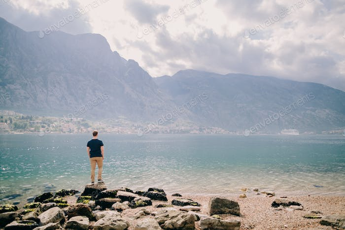 man travel rocky beach and mountains bay view