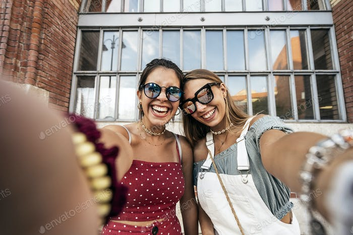 Happy young women in sunglasses taking selfie