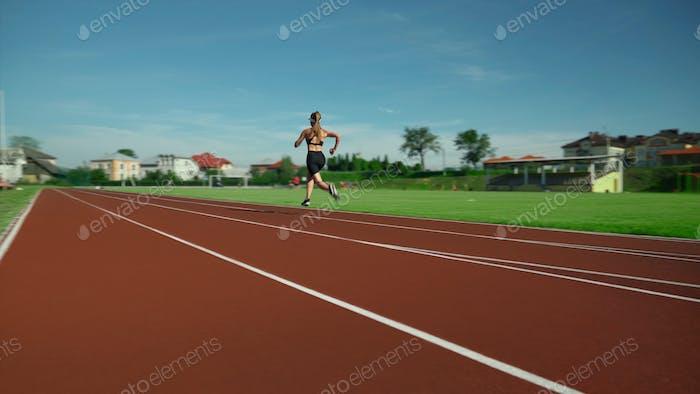 Unrecognizable athletic woman running at stadium