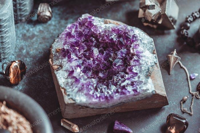 Amethyst Druze auf einem Hexenaltar für eine magische Zeremonie zwischen Kristallen und schwarzen Kerzen.