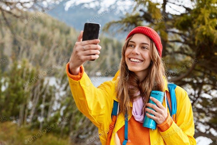 Glad lovely dark haired girl makes selfie portrait on cell phone, dressed in raincoat, headgear, wan