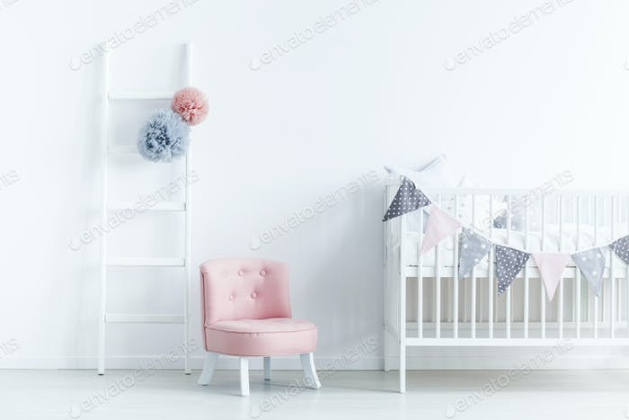 Pink chair next to white cradle in pastel baby's bedroom interio