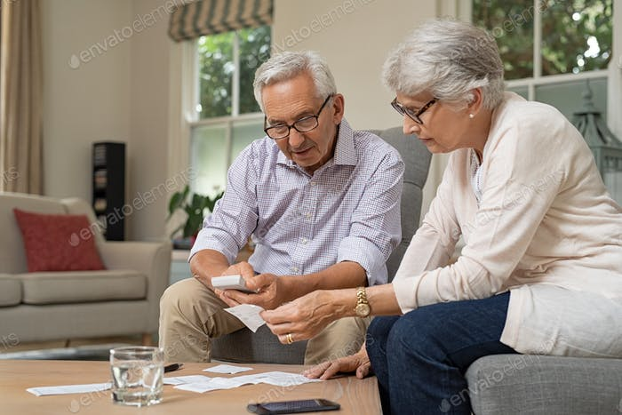 Senior couple calculating expenses