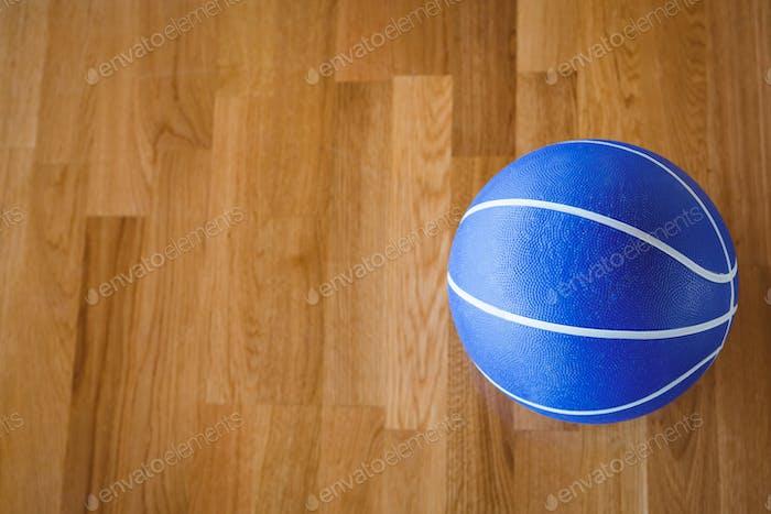 Overhead view of blue basketball on hardwood floor