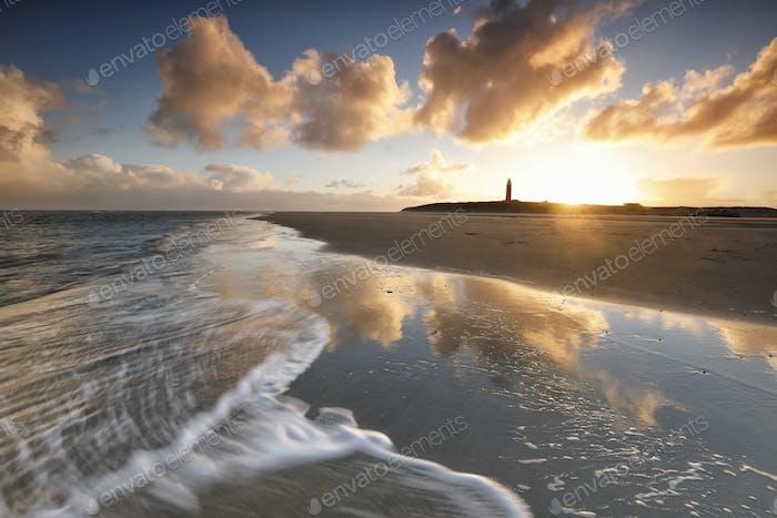gold dramatic sunrise over lighthouse
