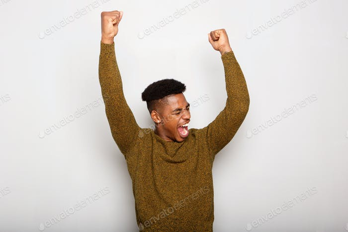 happy young black man with arms raised in joy against gray background