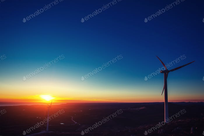 Solar wind turbines at sunset.