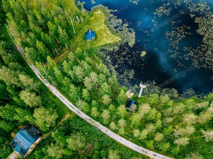 Vista Aéreo de House de De madera, sauna, barcos y muelle de pesca junto al lago.