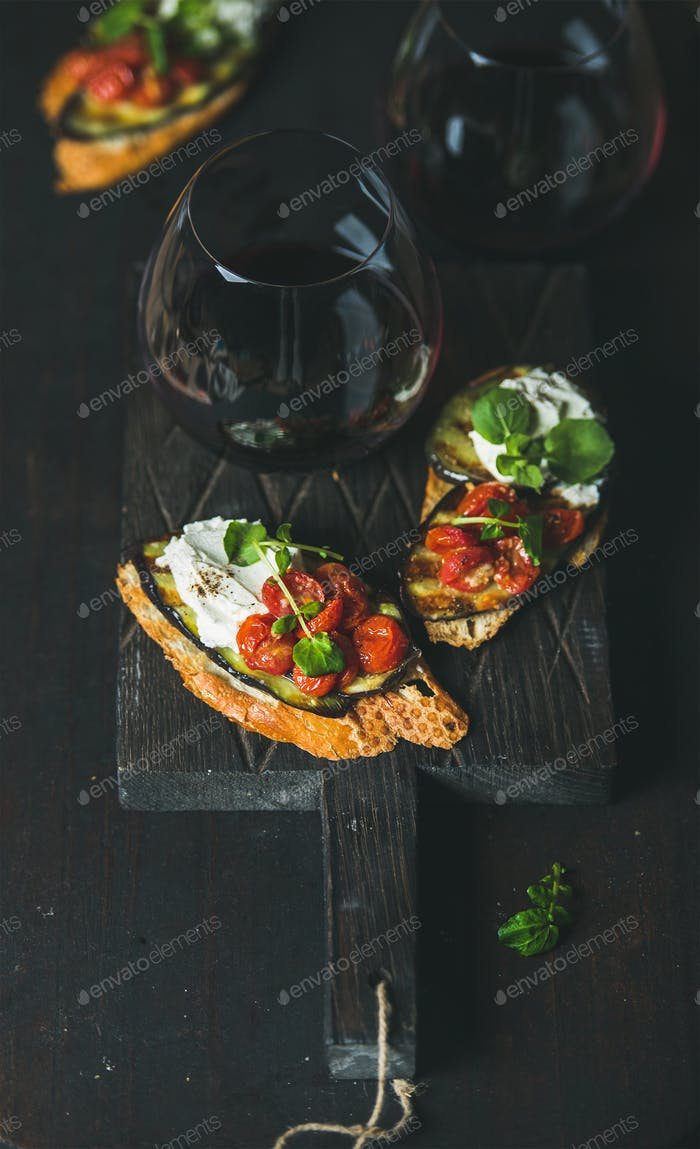 Wine and brushetta with eggplant, tomatoes, garlic, cream-cheese, arugula