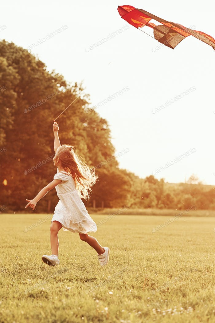 Vertical photo. Happy girl in white clothes have fun with kite in the field. Beautiful nature