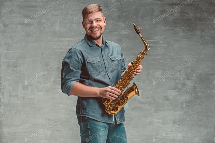 Happy saxophonist with sax over gray background