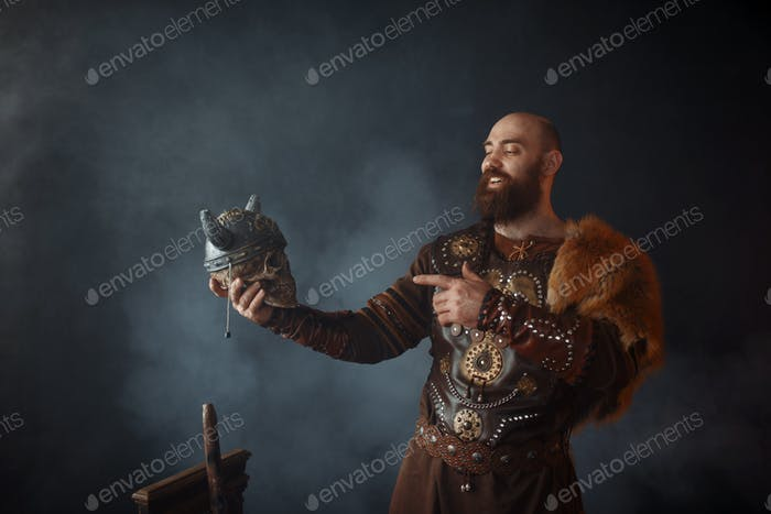 Smiling viking holds enemy's skull in helmet