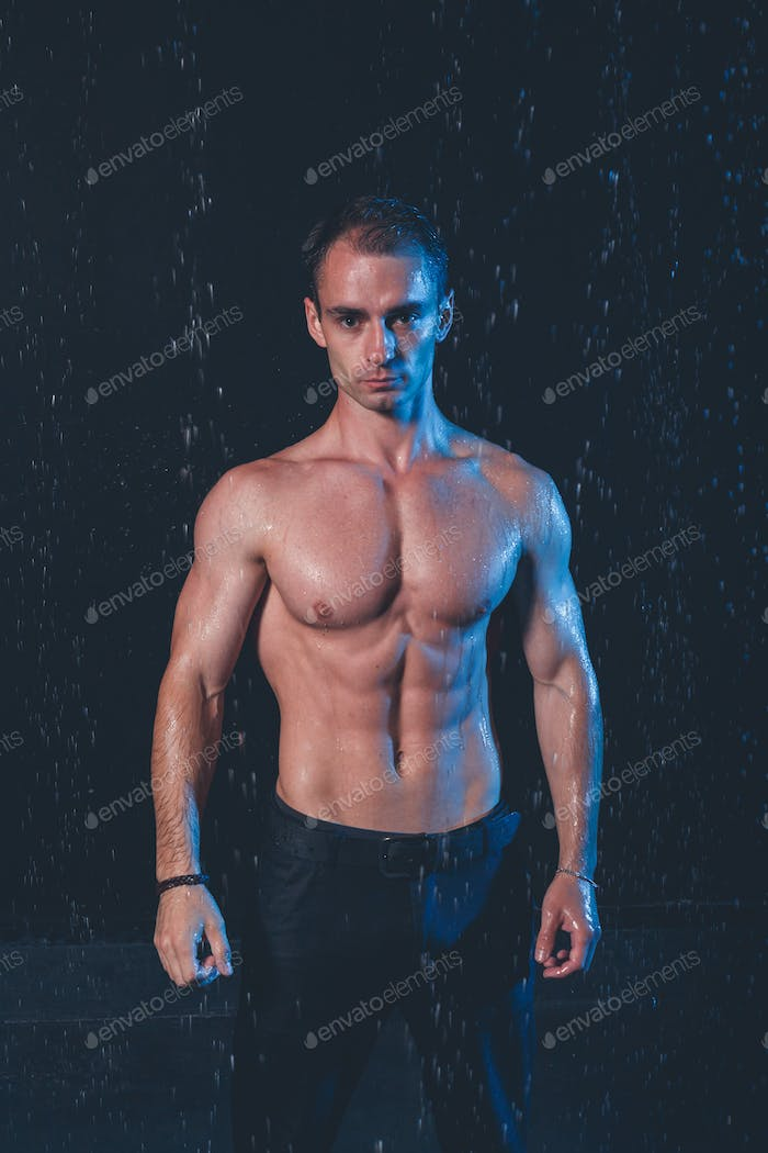 Fresh portrait of muscular man with water splashes on dark background.