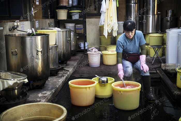 Japanese woman in a textile plant dye workshop, dyeing pieces of fabric in yellow plastic buckets,