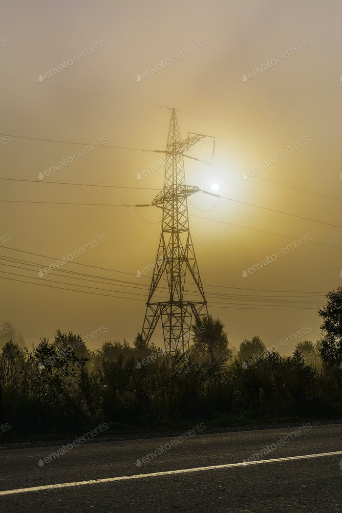 High voltage transmission tower near rural road