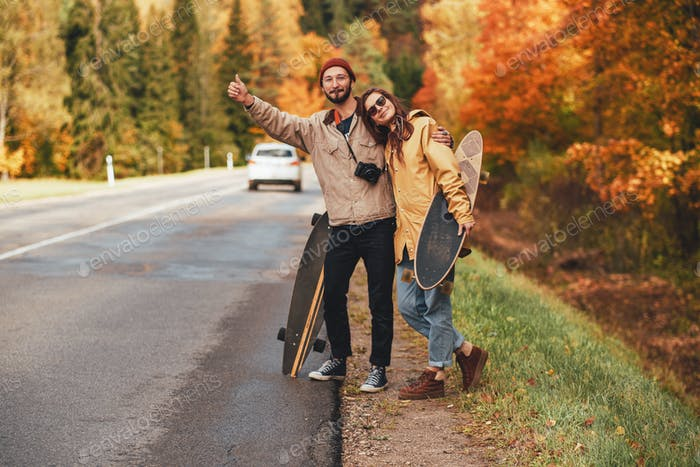 Embracing couple trying hitchhiking in autumn forest
