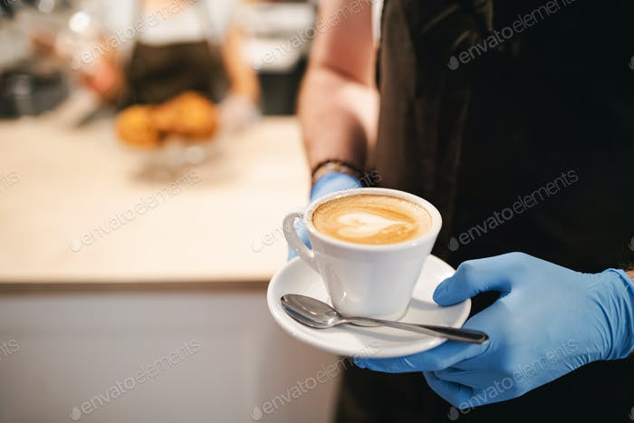 Unrecognizable waitress with gloves working in cafe, holding cup of coffee
