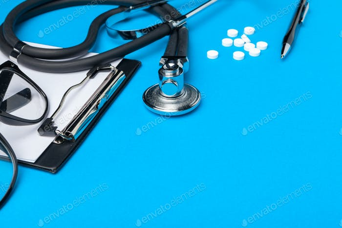Stethoscope, clipboard and pills, closeup. Medical equipment