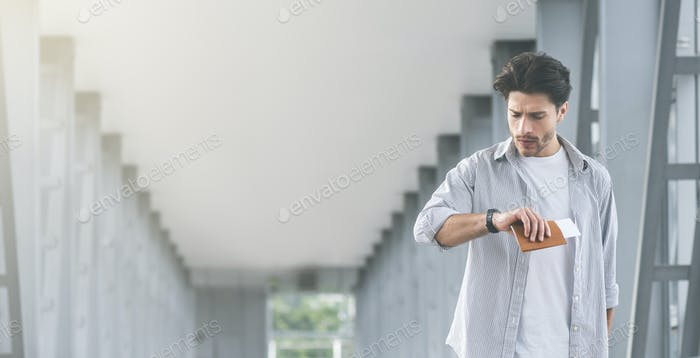 Man looking at wristwatch, going to flight with passport and tickets