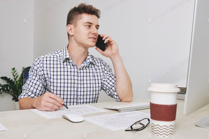 Designer talking on phone with customer
