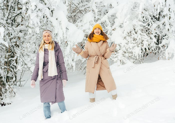 Two laughing friendly women stand in snowdrifts in the forest.  Frosty day, winter clothes