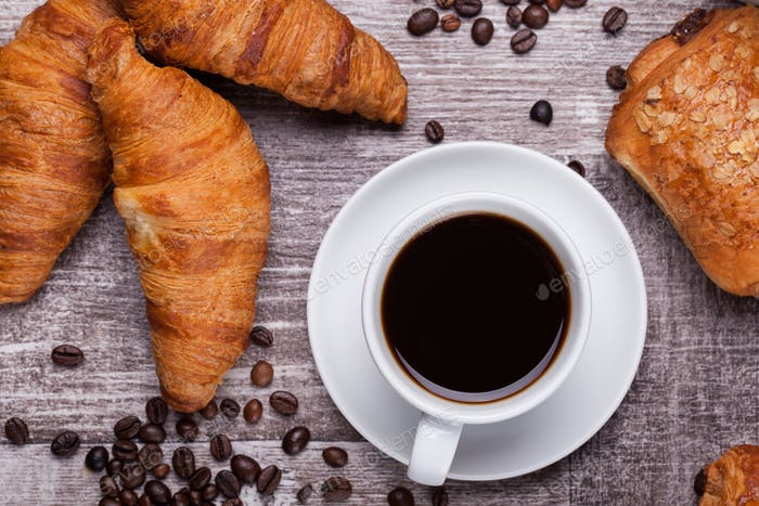 Cup of hot coffee and freshly baked croissants on dark wooden table