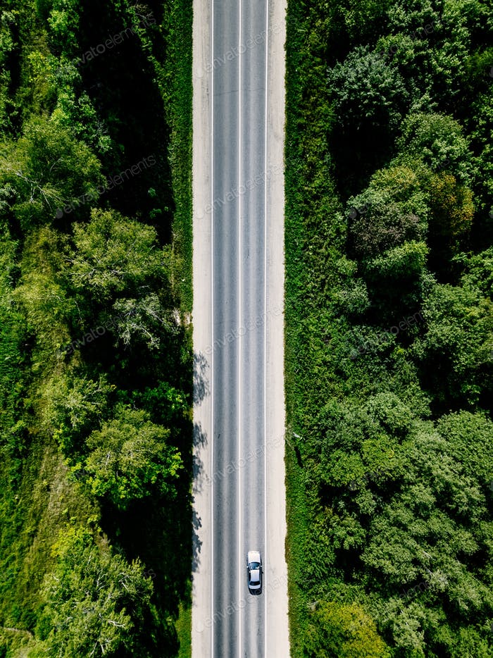 Aerial view  of road through the green forest in rural country